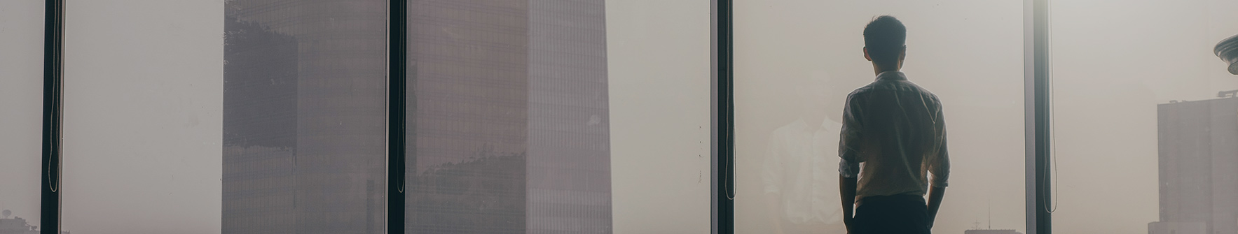 Businessman looking out of a commercial office building